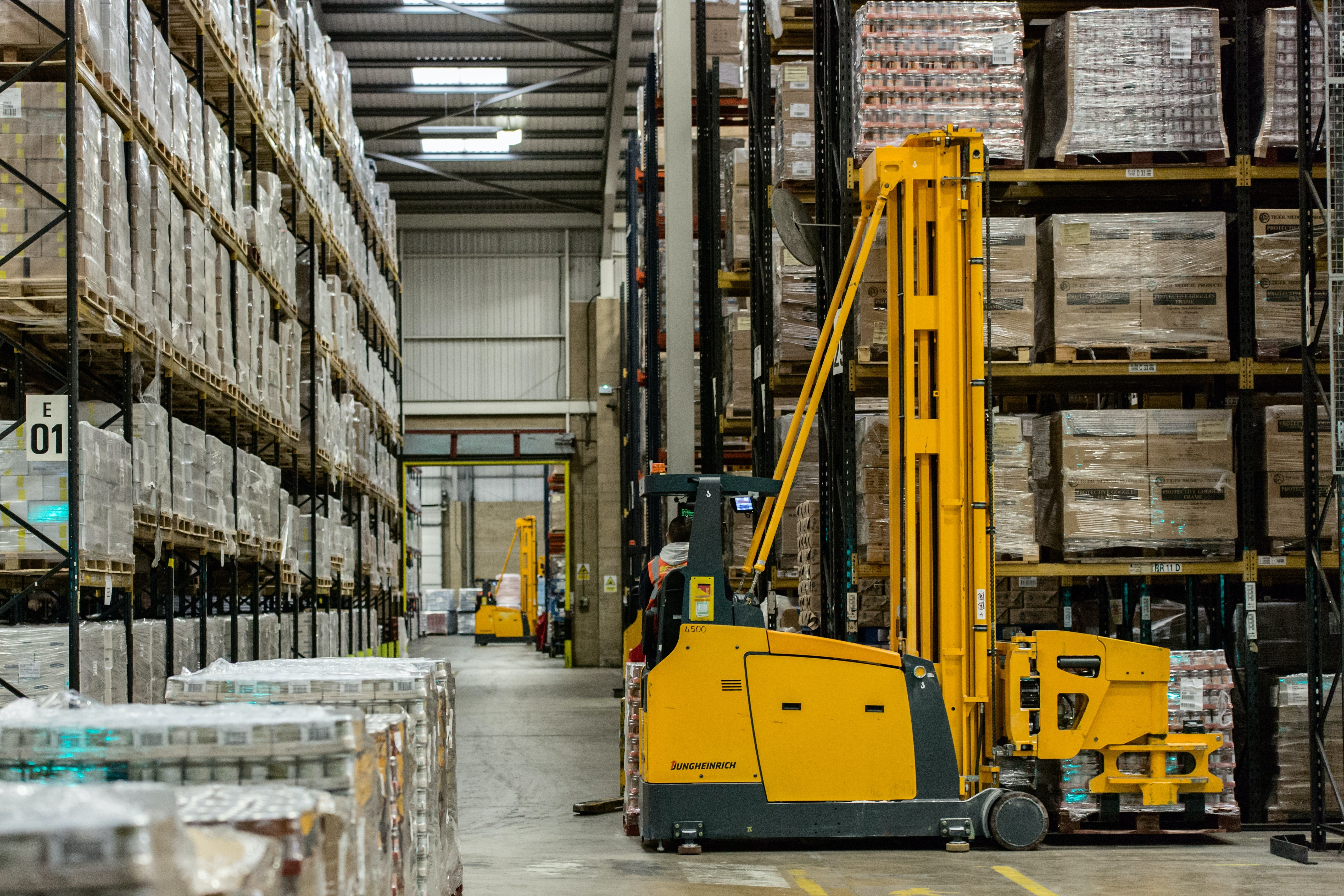 Warehouse aisle with  boxes on shelves and yellow black equipment