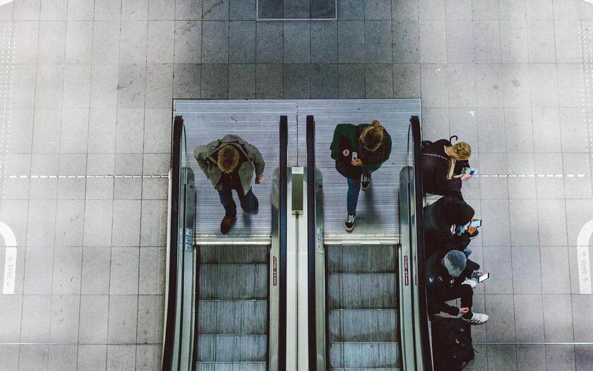 aerial view of two escalators and people looking at their phones