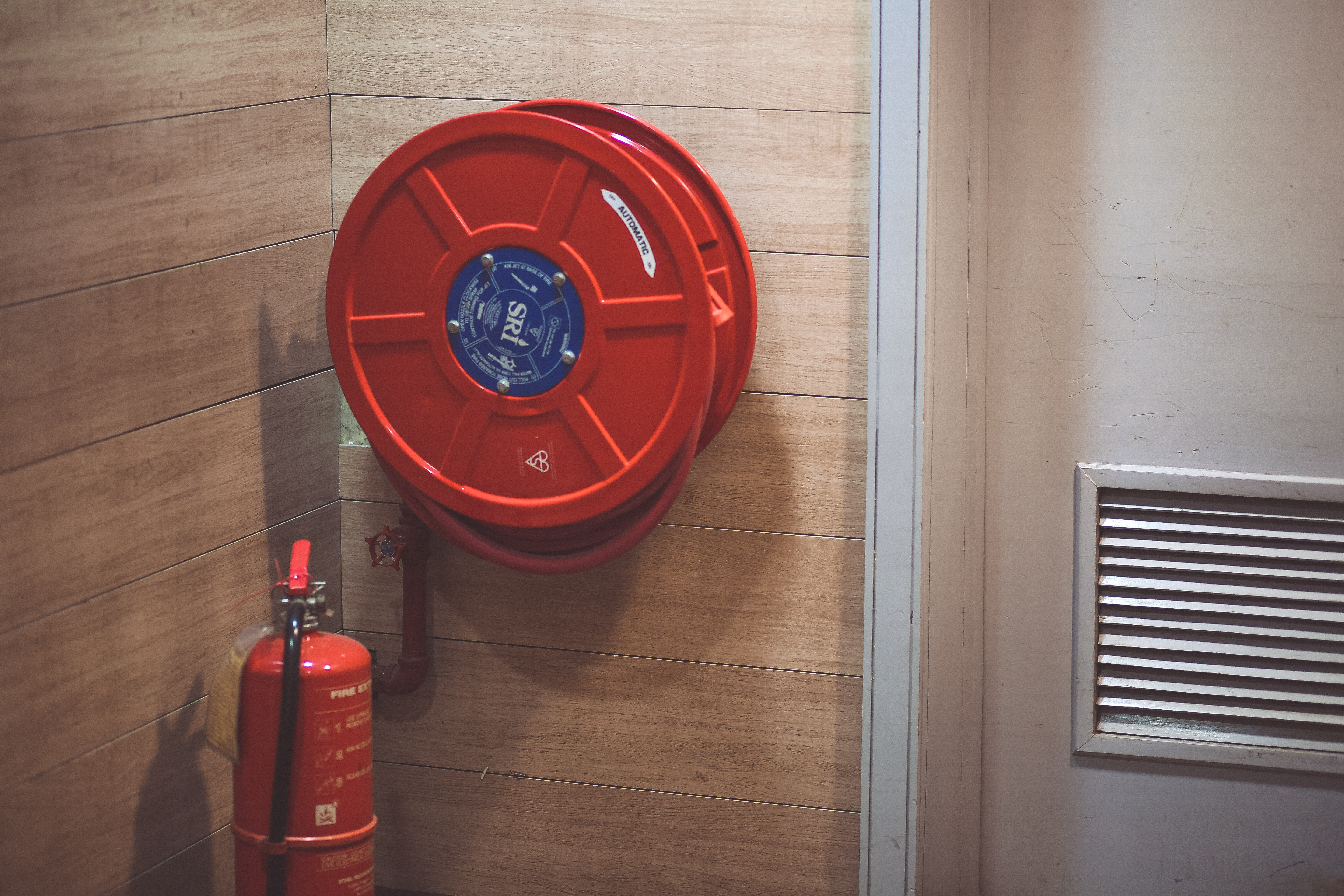 fire extinguisher and hose mounted on a building interior wall
