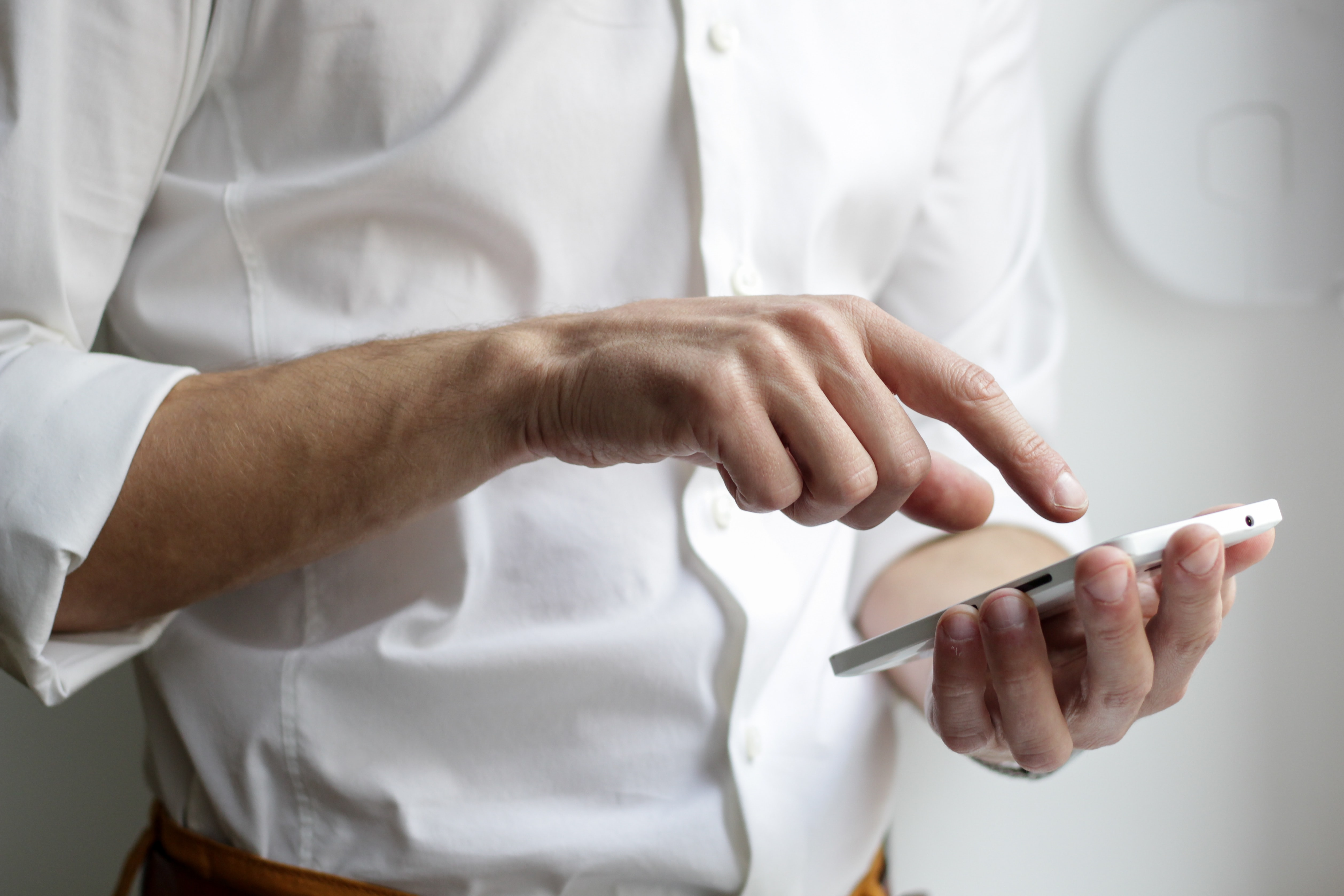 man in dress shirt holding phone