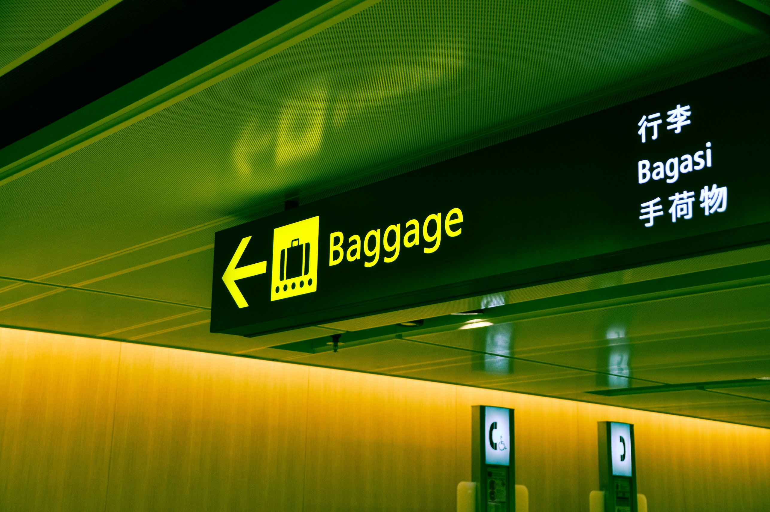 sign pointing to baggage claim in airport