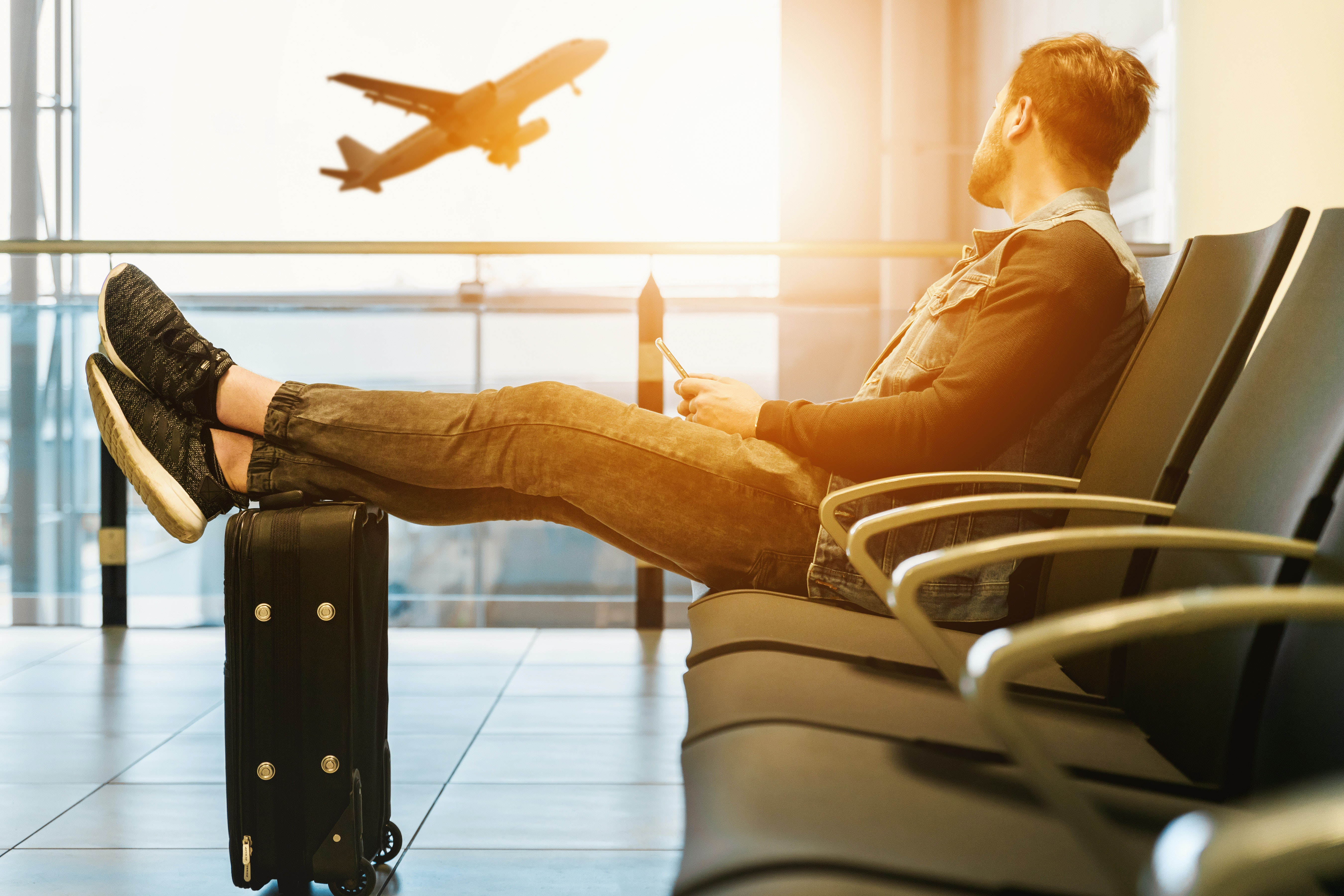 man sitting in airport on phone with feet on luggage