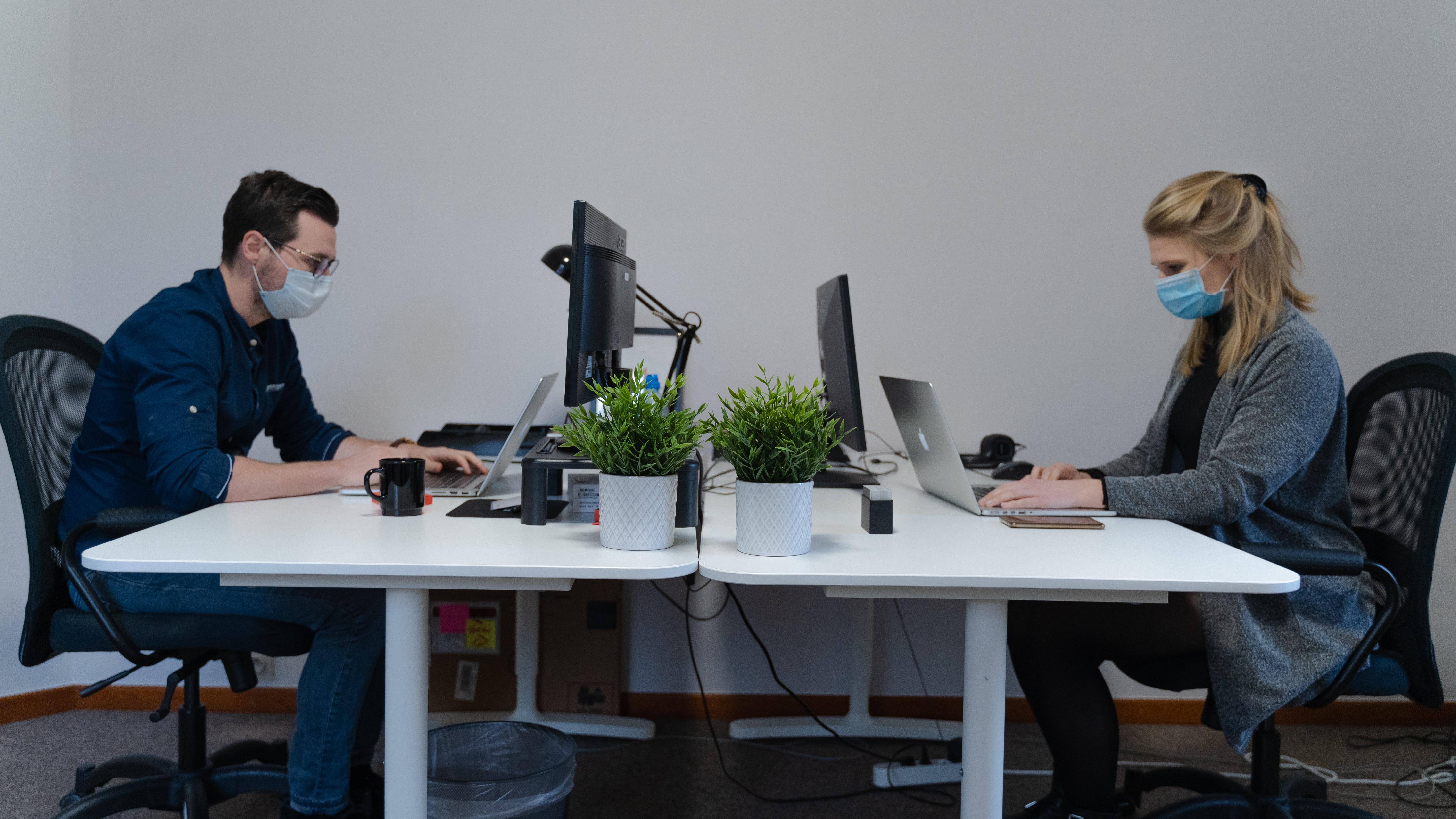 two employees with masks social distancing in office